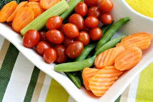A veggie platter with carrot coins, sugar snap peas, and cherry tomatoes