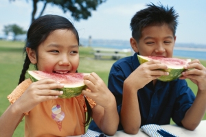 Two elementary school children sitting beside each other and eating watermelon wedges at a picnic table
