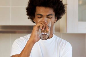 A young man drinking a glass of water in a kitchen
