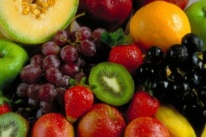 Full-frame picture of fruit including cantaloupe, grapes, apples, oranges, kiwi, and strawberries