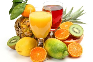 Two glasses of fruit juice surrounded by fresh fruit