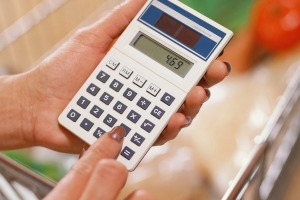 Close-up of a woman using a calculator at the grocery store