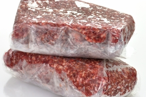 Two one-pound packages of frozen ground beef wrapped in clear plastic