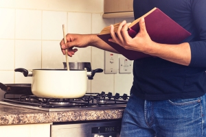 A man reading a cookbook and stirring a pot on the stove.
