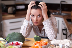 A woman with her hands on her head in exasperation and stress amidst chopping vegetables.