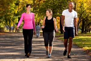 Two women and a man wearing athletic clothing and walking side by side in a park.