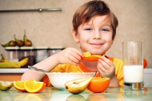 Young boy eating orange slices at the kitchen table.