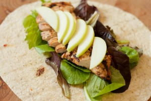 Apple slices and grilled chicken over lettuce in an open flour tortilla.