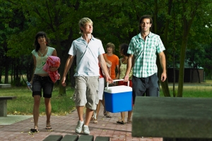 A group of people with two young men carrying a cooler and walking towards a picnic table.