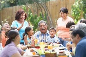 Hispanic family gathered around a picnic table.