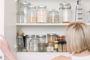 Woman looking into an organized kitchen cabinet.
