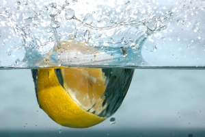 Lemon half splashing into water.