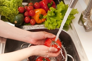 Close-up of a woman washing tomatoes in a colander in the sink.