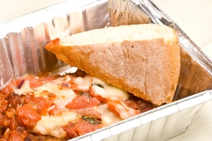 Lasagna and bread in an aluminum to-go container.