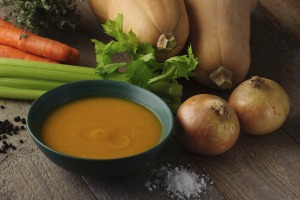 A bowl of butternut squash soup with whole celery, carrots, onions, and butternut squash next to it.