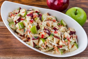 A bowl of cole slaw with apples.