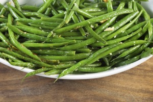 Close up of a bowl of whole sauteed green beans.